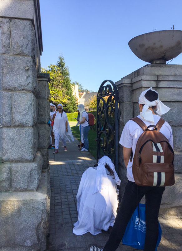 students at the cemetery gate, greeting Eshu before entering