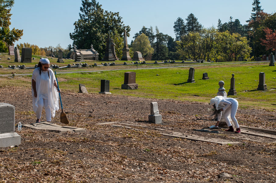 Shy Pacheco Hamilton and student sweeping the cemetery, 2017