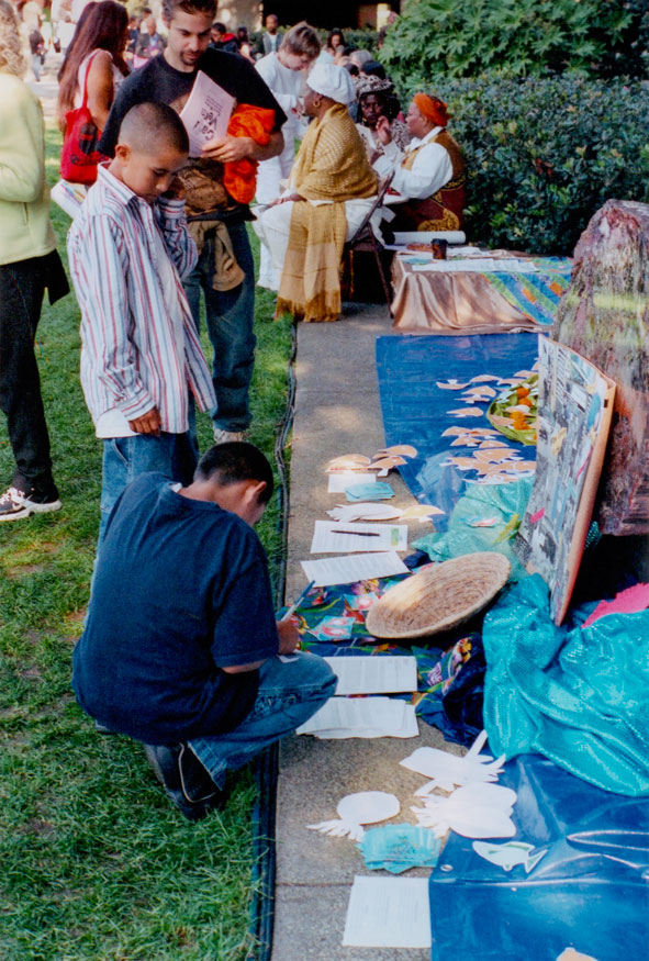 visitors writing prayers on paper fish to add to the altar